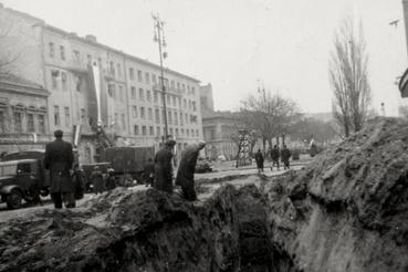 Balra a Köztársaság téri pártszékház, amelyet október 30-án a forradalmárok megostromoltak. A fotó előterében az Erkel Színház előtt ásott árkok.Az ávósok titkos pincebörtöneiről akkoriban rémhírek terjedtek. Bár Pölöskei János is emlékszik a téren hallott beazonosíthatatlan, leginkább dobogásra hasonlítható hangokra, a Kerepesi temetőig terjedő kazamatarendszer léte mindeddig városi legendának bizonyult.